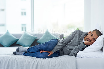 Buy stock photo Full length shot of a young man lying on his bed while feeling unwell at home