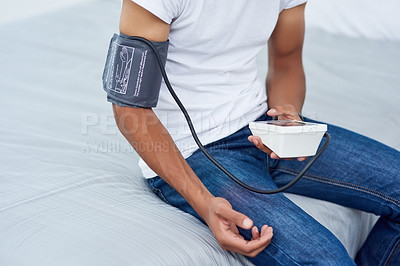 Buy stock photo High angle shot of an unrecognizable man taking his blood pressure while sitting on the bed at home