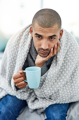 Buy stock photo Cropped shot of a young man sitting on his bed with a cup of tea while feeling unwell at home