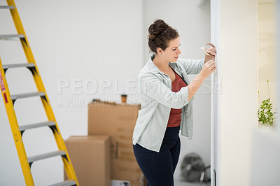 Buy stock photo Cropped shot of an attractive young woman taping up the fittings and fixtures in her home