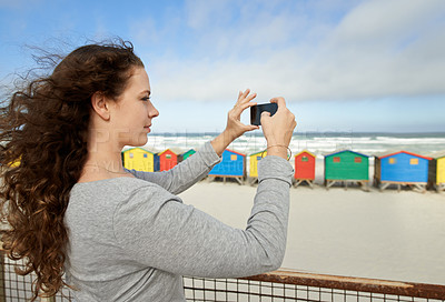 Buy stock photo Shot of a young woman taking pictures with a smartphone at the beach