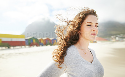 Buy stock photo Shot of a young woman spending a day at the beach