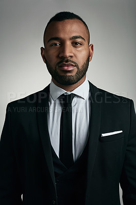 Buy stock photo Cropped portrait of a handsome young businessman posing against a gray background