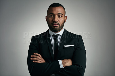 Buy stock photo Cropped portrait of a handsome young businessman standing with his arms folded against a gray background