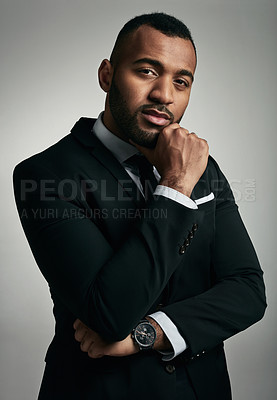 Buy stock photo Cropped portrait of a handsome young businessman standing with his hand on his chin against a gray background