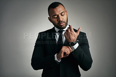 Buy stock photo Cropped shot of a handsome young businessman adjusting his cuffs while against a gray background