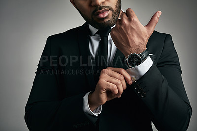Buy stock photo Cropped shot of an unrecognizable young businessman adjusting his cuffs while against a gray background