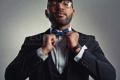 Buy stock photo Cropped portrait of a handsome young businessman adjusting his bowtie while against a gray background