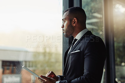 Buy stock photo Cropped shot of a handsome young businessman working on his tablet in a modern office