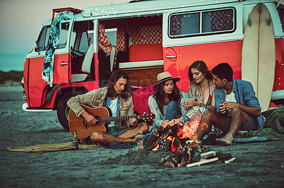Buy stock photo Shot of a group of friends sitting around a fire on the beach