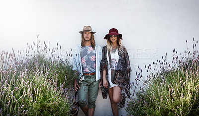 Buy stock photo Cropped shot of a trendy young couple standing together against the wall of a building outside
