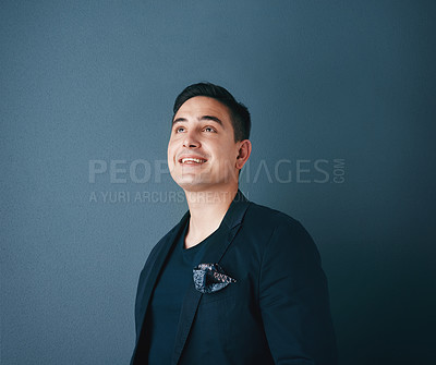 Buy stock photo Studio shot of a handsome young man posing against a blue background