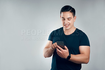 Buy stock photo Studio shot of a handsome young man using a cellphone against a grey background