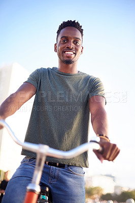 Buy stock photo Low angle shot of a young handsome man riding a bicycle on the promenade at the beach