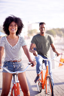 Buy stock photo Cropped shot of a young attractive couple cycling along the promenade at the beach