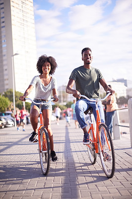 Buy stock photo Shot of a young attractive couple cycling along the promenade at the beach