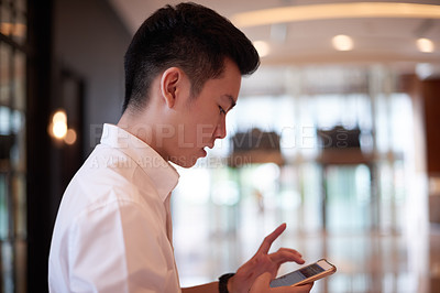 Buy stock photo Shot of a carefree young man texting on his cellphone while standing inside of a building during the day