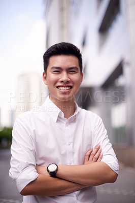 Buy stock photo Portrait of a confident young man standing with his arms folded outside in a street during the day