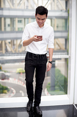 Buy stock photo Shot of a confident young businessman standing in the office while texting on his cellphone  during the day