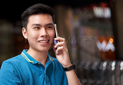 Buy stock photo Shot of a cheerful young man talking on his cellphone whole standing in the busy streets of the city outside during the day