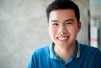 Buy stock photo Portrait of a cheerful young man  seated at work next to a window while looking directly at the camera during the day
