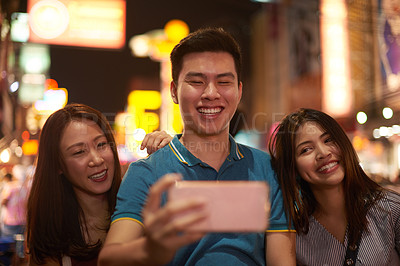 Buy stock photo Shot of happy young friends taking a selfie with a mobile phone on a night out in the city