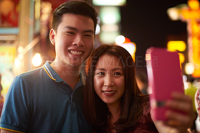 Buy stock photo Shot of a young couple taking a selfie with a mobile phone on a night out in the city
