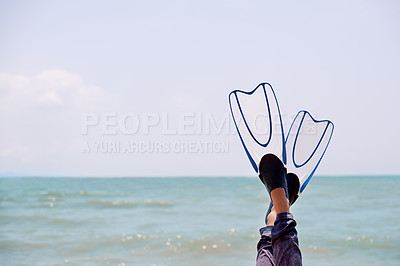 Buy stock photo Cropped shot of an unrecognizable woman's feet in flippers at the beach