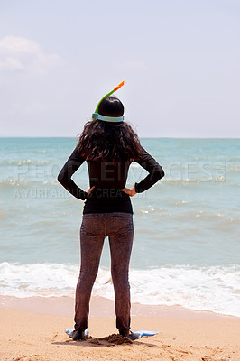 Buy stock photo Rearview shot of an unrecognizable young woman wearing her snorkelling gear at the beach