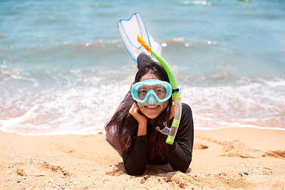 Buy stock photo Full length portrait of an attractive young woman wearing her snorkelling gear while lying on the beach