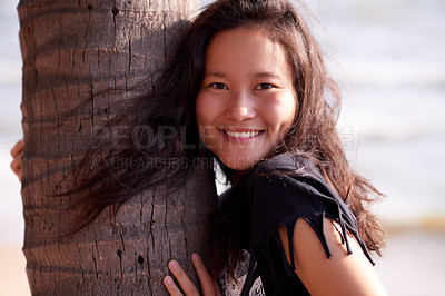 Buy stock photo Cropped portrait of an attractive young woman enjoying a day at the beach