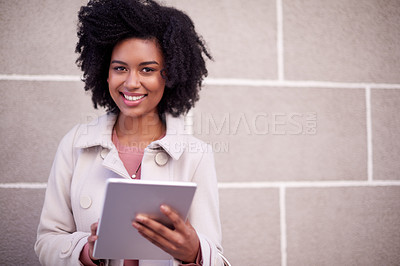 Buy stock photo Cropped portrait of an attractive and fashionable young woman using her tablet while out in the city