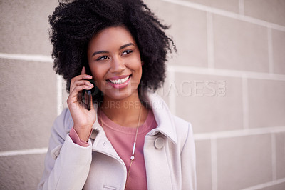 Buy stock photo Cropped shot of an attractive and fashionable young woman making a phonecall while walking in the city
