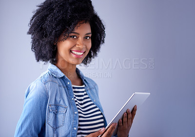 Buy stock photo Studio portrait of a young woman using a digital tablet against a purple background