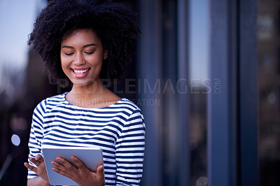 Buy stock photo Shot of a young designer using a digital tablet outside an office