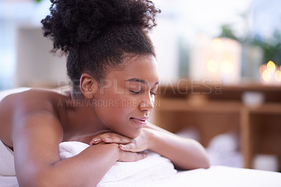 Buy stock photo Shot of a young woman relaxing on a massage bed at a spa