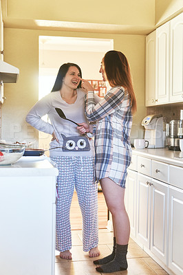 Buy stock photo Shot of two young women making breakfast in the kitchen at home
