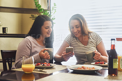Buy stock photo Cropped shot of two young women using a cellphone together while having breakfast in the morning at home