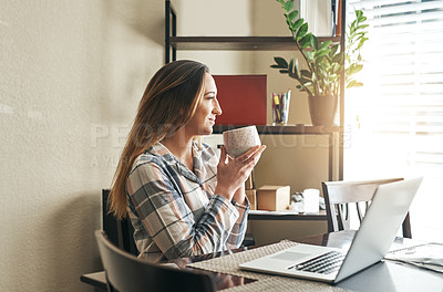 Buy stock photo Cropped shot of a young woman drinking coffee and using a laptop in the morning at home