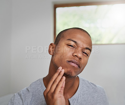 Buy stock photo Portrait of a handsome young man examining his face in the bathroom mirror