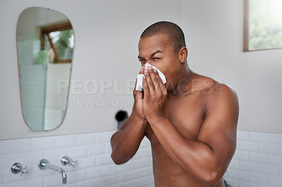Buy stock photo Shot of a handsome young man blowing his nose in the bathroom at home