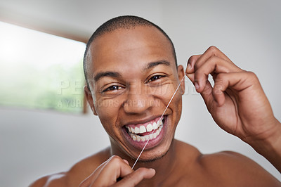 Buy stock photo Portrait of a handsome young man flossing his teeth in the bathroom at home