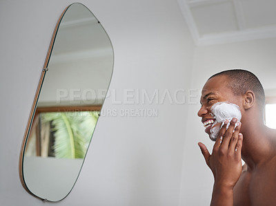 Buy stock photo Shot of a handsome young man applying shaving cream to his face in the bathroom at home
