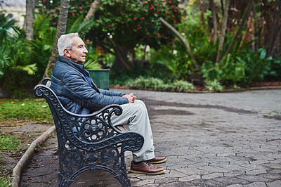 Buy stock photo Shot of a senior man sitting on a park bench and looking thoughtful