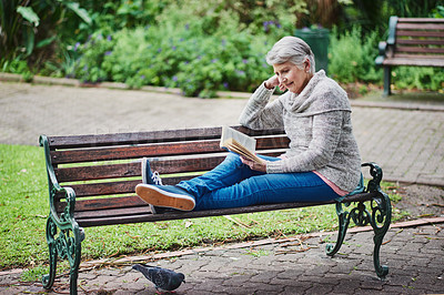 Buy stock photo Shot of a senior woman reading a book and relaxing in the park