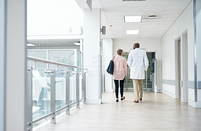 Buy stock photo Rearview shot of a mature handsome male doctor talking to a female patient in the hospital corridor