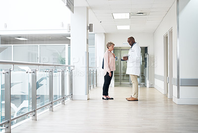 Buy stock photo Full length shot of a handsome mature male doctor talking to a female patient in the hospital corridor