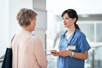 Buy stock photo Cropped shot of an attractive young female nurse talking to a mature patient in the hospital corridor