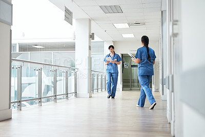 Buy stock photo Full length shot of two young female nurses walking through the hospital corridor