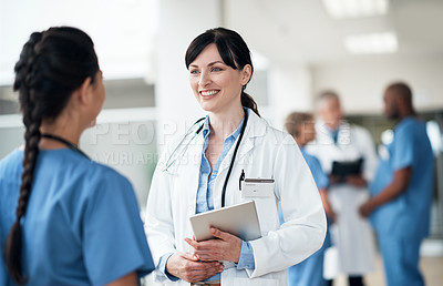 Buy stock photo Cropped shot of two attractive young female medical workers talking while standing in the hospital corridor